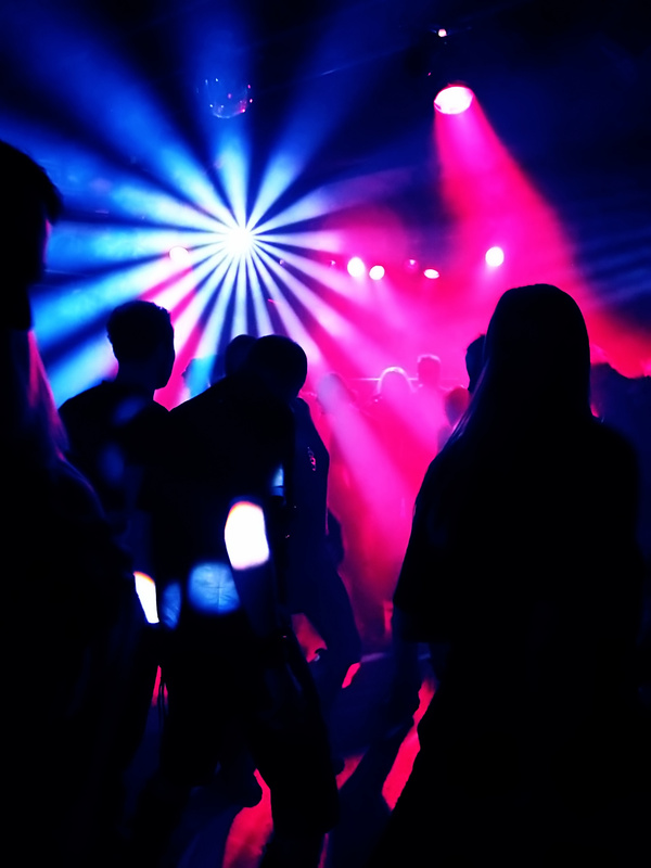 Disco party scene with people dancing and disco lights.